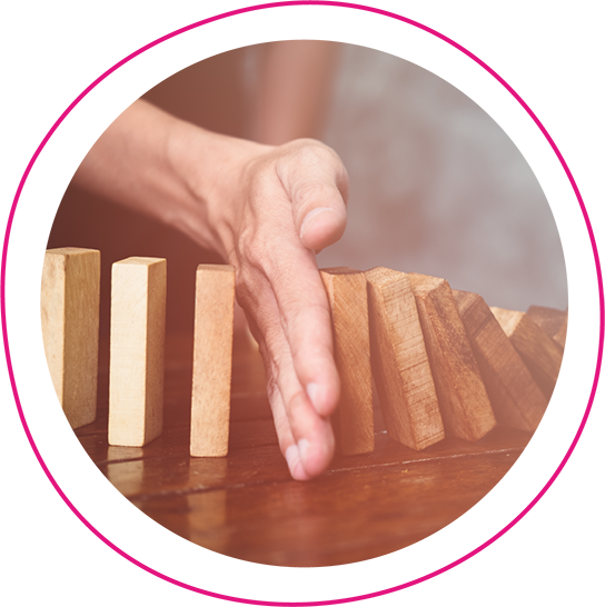Person trying to stop building blocks creating the domino effect by putting their hand in the way of the falling blocks
